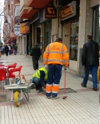 trabajadores sustituyen las viejas baldosas rotas o desaparecidas por otras nuevas